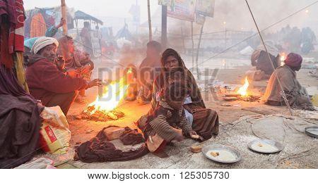 ALLAHABAD, UTTAR PRADESH, INDIA - FEBRUARY 11, 2013: unidentified poor Indian beggar family is warming oneself at the fire at Maha Kumbh Mela festival.