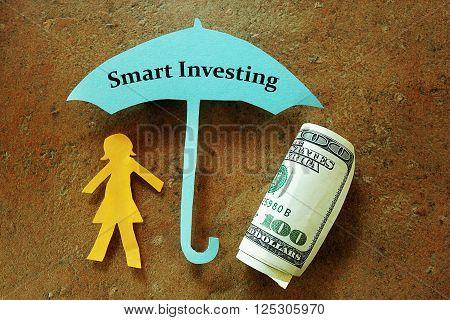 Paper woman under a Smart Investing umbrella