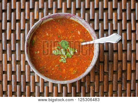 Overhead view of a bowl of freshly made gazpacho soup with cilantro garnish poster