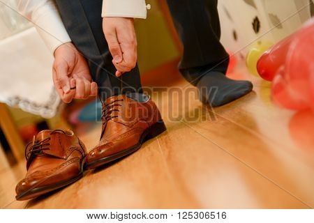 Man tied shoelace to his bown shoes in natural light