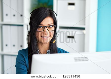 Portrait Of Female Operator With Headset Smiling At Camera In Call Center