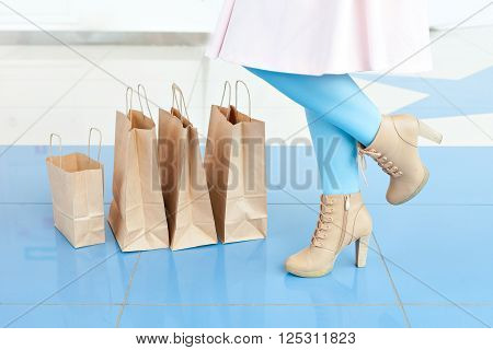 Legs of a woman in a light blue tights and beige shoes near shopping bags. Shopping at the mall. Copy space. Legs and bags. mischievous mood.