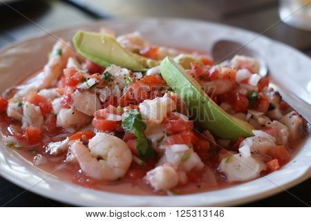 A colorful seafood ceviche appetizer served on a white plate.