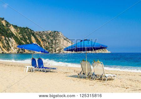 Sunbeds and umbrellas (parasols) on the beach. View of beautiful Petani beach and Petani bay, Kefalonia island, Greece.