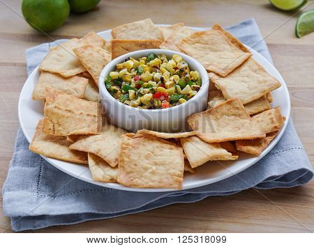 Corn Salsa with Pita Chips on Wood Background. Selective focus.