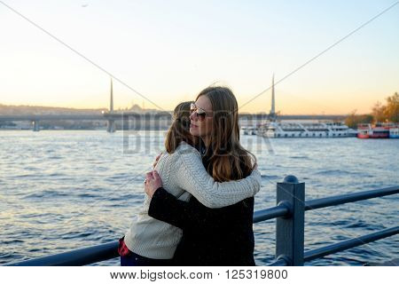 Hugging Young Mother With Her Daughter On The Background Bosphorus In Istanbul