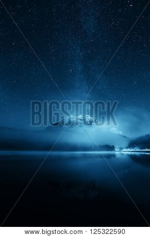 Snow mountain with fog over lake with milky way