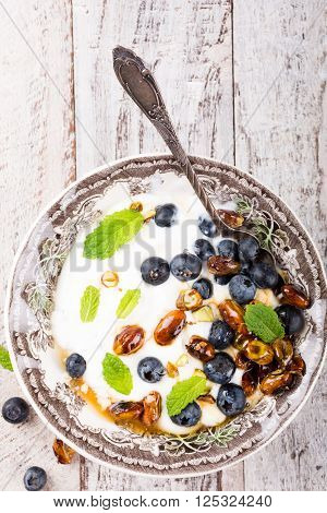 Healthy breakfast, quark with blueberries, pistachios and mint on light wooden background. Top view with copy space.