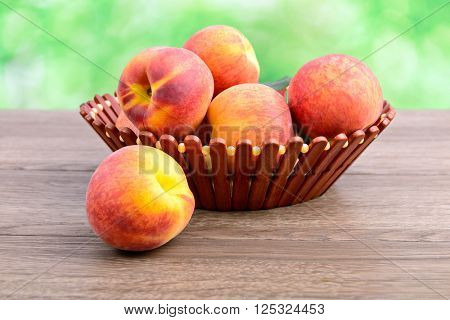 Ripe peaches in basket on green background