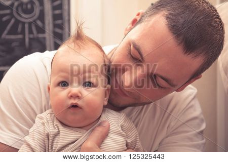 Father embracing his little baby. Father is looking on baby, baby is looking on camera. Baby with funny haircut