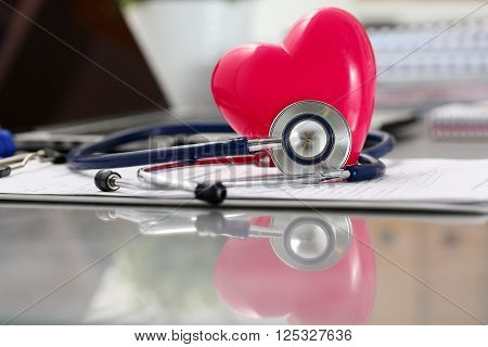 Medical Stethoscope Head And Red Toy Heart Lying On Cardiogram Chart