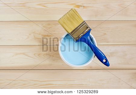 brush blue paint in a bucket on wooden boards