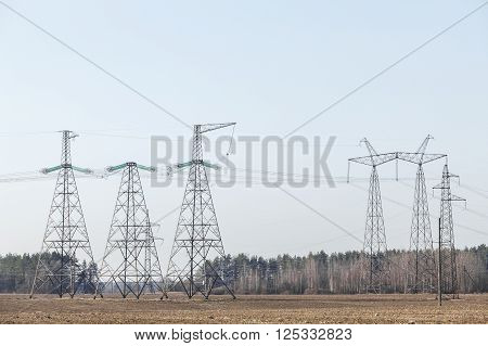 electricity transmission pylon silhouetted against blue sky. In the woods, at sunset.