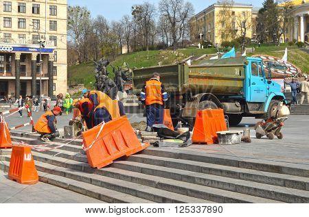 Utility workers in orange vests repair after riot and vandalism 2013-2014. Khreshatik - central street of Kiev.At April 8,2016 in Kiev, Ukraine
