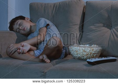 Small Boy Sleeping On The Couch While Watching Tv And Eating Popcorn At Night In The Living Room