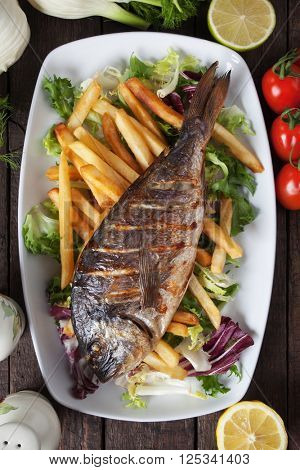 Grilled bream fish with french fries and salad
