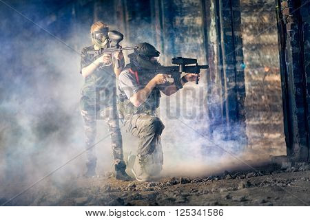 Two friends in paintball club during game