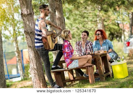 Tattooed guy with guitar and song gives joy to his friend in summer camp while drinks beer