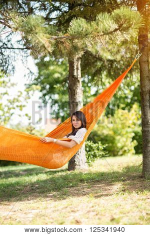 Young nice girl resting in hammock in nature