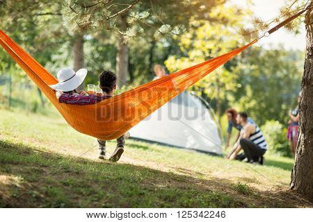 Love couple photographing from back in orange hammock in nature