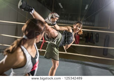 energy women practicing body combat attack in boxing ring