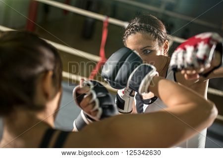 energy female boxer practicing in the boxing ring
