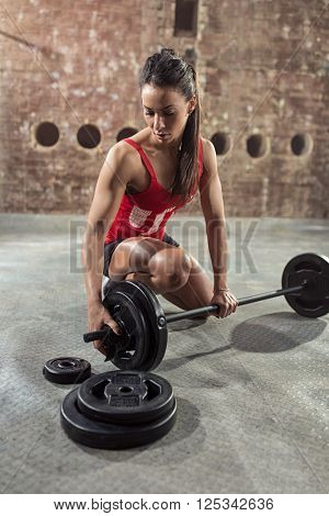 Attractive muscular woman with dumbbell