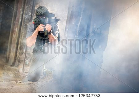 Young paintball player shooting thought smoke