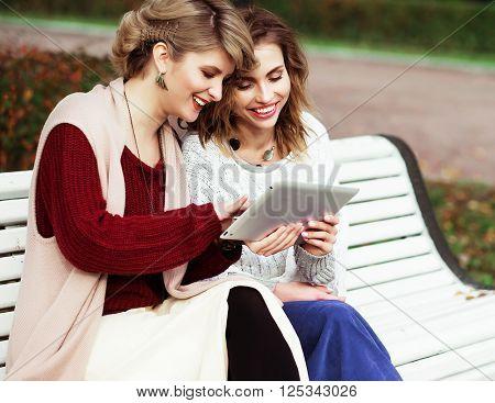 beautiful women girls autumn using tablet outdoor