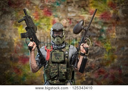 Handsome paintball gamer with guns in camouflage uniform