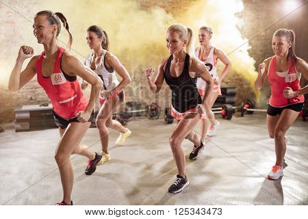 Group of young women in running pose, high-energy fitness class