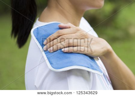 woman putting an ice pack on her shoulder pain