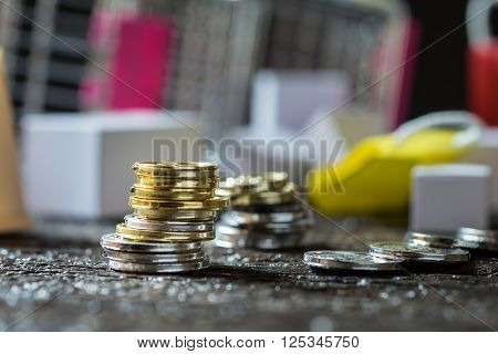 Coins stacked on each other in different positions. Money concept. Shopping trolley. Shopping cart in the background