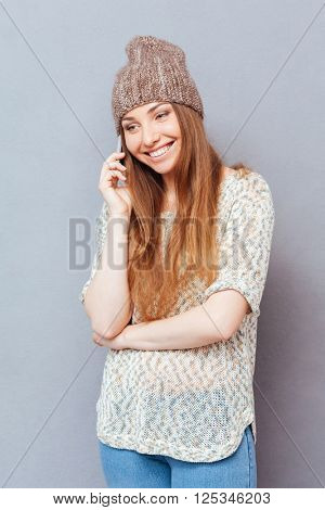 Happy woman talking on the phone and looking away over gray background