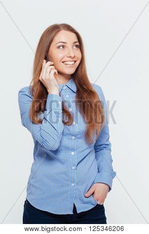 Happy woman talking on the phone and looking away isolated on a white background