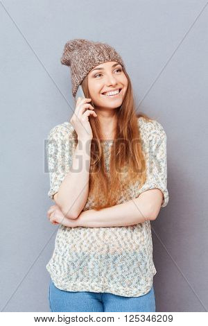 Cheerful casual woman talking on the phone over gray background