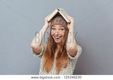 Cheerful woman holding book on head and looking at camera