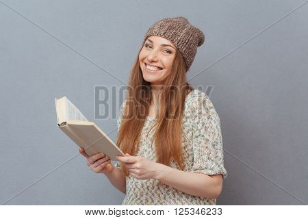 Happy woman holding book over gray background and looking at camera