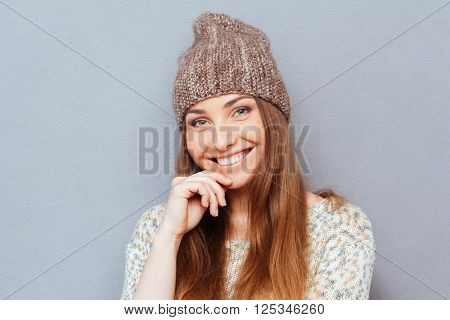 Charming happy woman looking at camera over gray backgorund
