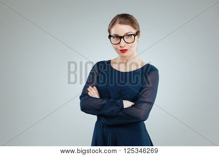 Beautiful serious woman in glasses looking at camera isolated on a white background