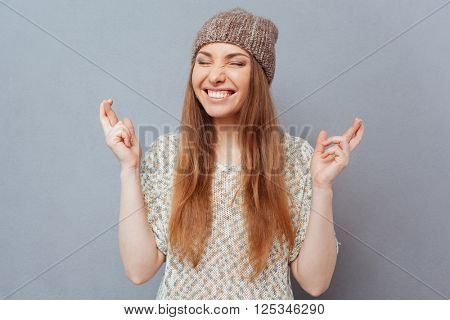 Smiling woman with crossed fingers standing over gray background
