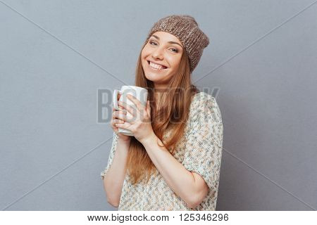 Smiling woman holding cup and looking at camera over gray background