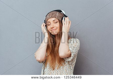 Happy woman with closed eyes listening music in headphones over gray background