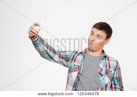 Funny man making selfie photo on smartphone isolated on a white background