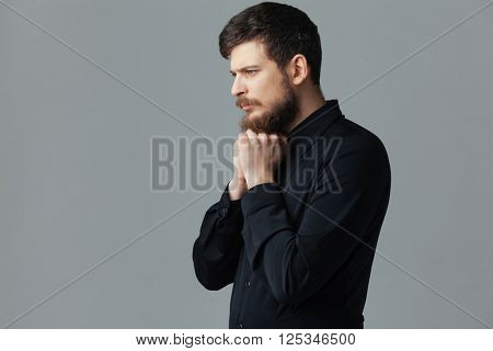Thoughtful businessman standing over gray background