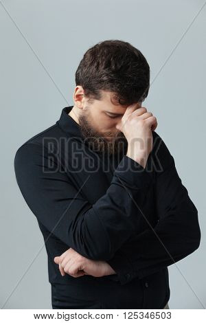 Young man thinking about something over gray background