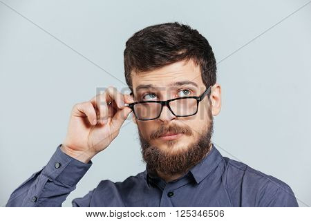 Pensive man in glasses looking up over gray background