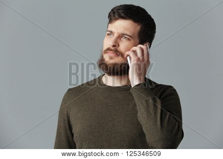 Casual man talking on the phone over gray background