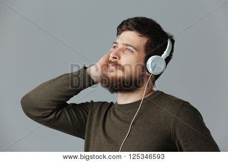 Handsome man listening music in headset over gray background