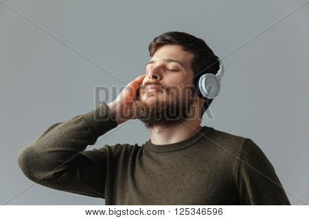Relaxed man listening music in headset over gray background